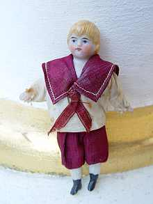 Antique dollhouse bisque doll, a cute little boy, dated about 1900.