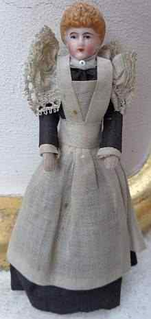 Antique dollhouse doll, a lovely maid with original old dress with long apron, made about 1910.