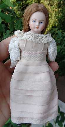 Antique dollhouse doll, a lovely doll maid with old pink dress, dated about 1900.